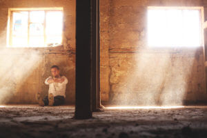 young man drinking alone in an empty building