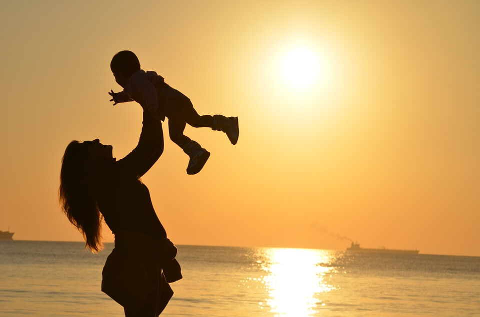 Silhouette of mother holding child up with sunset in the background
